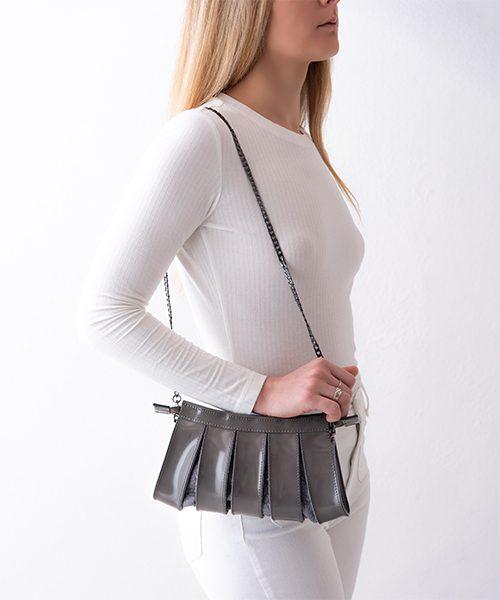 Pochette Nica small in vera pelle, colore grigio, con tracolla staccabile, indossata