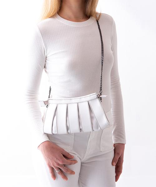 Pochette Nica in pelle di colore bianco, con tracolla staccabile, indossata da modella