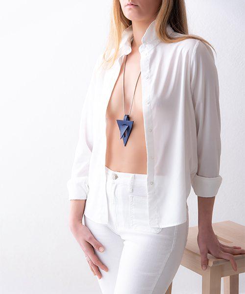 Collana con pendente in pelle di colore blu, catena in acciai. Collana indossata da modella vestita in bianco