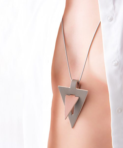 Collana con pendente in pelle di colore rosa/fango , catena in acciaio. Collana indossata da modella vestita in bianco