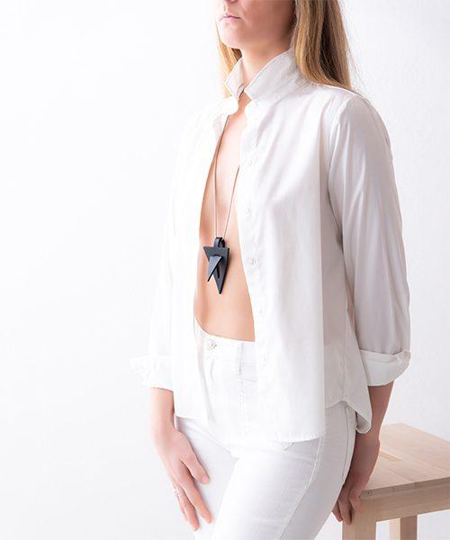 Collana con pendente in pelle di colore nero , catena in acciaio. Collana indossata da modella vestita in bianco