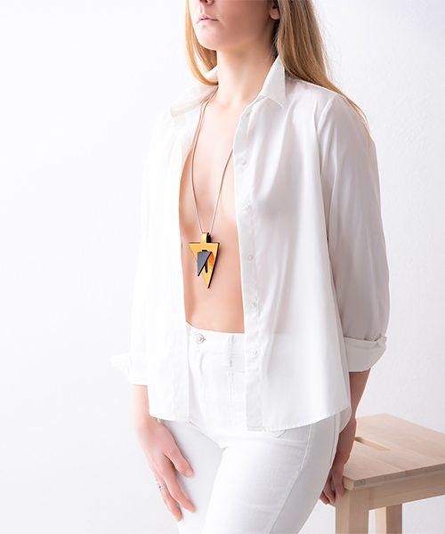 Collana con pendente in pelle di colore oro/nero , catena in acciaio. Collana indossata da modella vestita in bianco