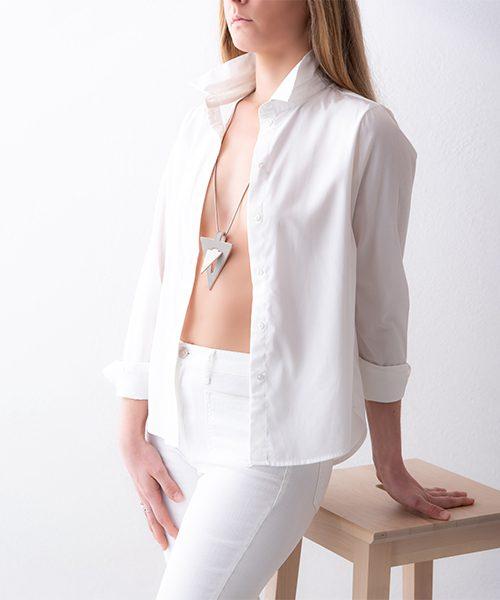 Collana con pendente in pelle di colore bianco sporco/grigio chiarissimo, catena in acciai. Collana indossata da modella vestita in bianco