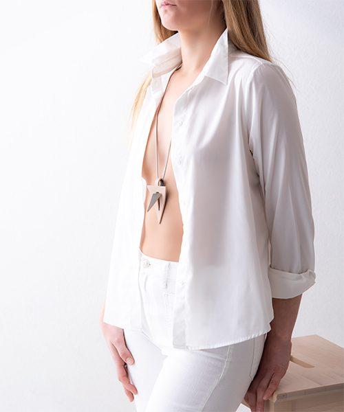 Collana con pendente in pelle di colore rosa chiaro/marrone, catena in acciaio. Collana indossata da modella vestita in bianco