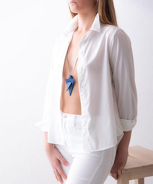 Collana con pendente in pelle di colore azzurro , catena in acciaio. Collana indossata da modella vestita in bianco