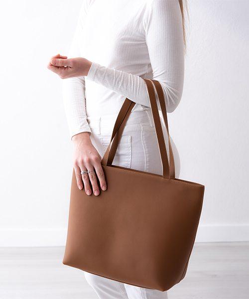 Borsa shopper Linea in vera pelle, con manici a spalla, colore cuoio. Indossata da modella