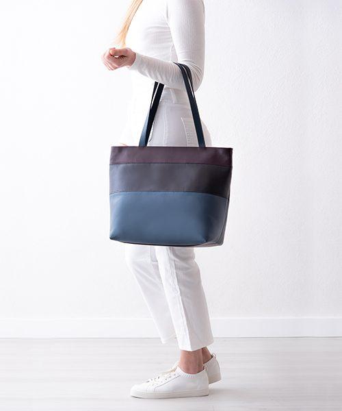 Borsa a spalla Linea, in vera pelle, colore blu, prugna e viola scurissimo.indossata da modella
