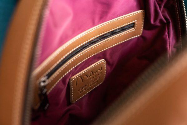 zaino in pelle color cuoio, dettaglio interno fodera bordeaux, taschino con zip