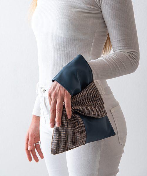 Pochette Kyo da polso in vera pelle, colore blu e beige. Indossata da modella.