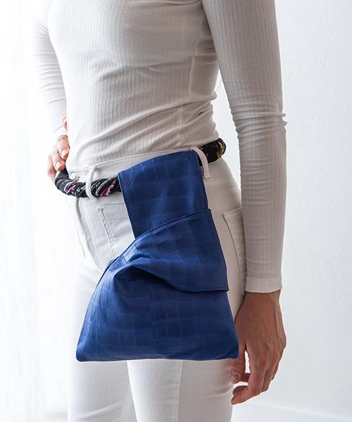 Pochette Kyo da polso, in vera pelle, colore blu sport. Indossata come marsupio.