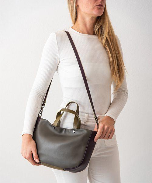Borsa Tita, graziosa e capiente realizzata in nappa, colore grigio, viola scuro e verde. Indossata con la tracolla.