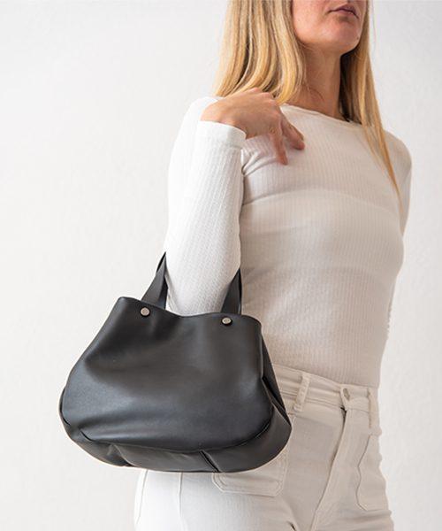 Borsa Tita, graziosa e capiente realizzata in nappa, colore nero. Indossata a mano.