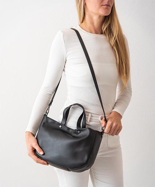 Borsa Tita, graziosa e capiente realizzata in nappa, colore nero. Indossata con la tracolla.